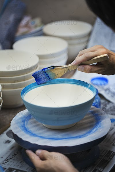 Close up of person working in a Japanese porcelain workshop, painting white bowls with blue glaze.