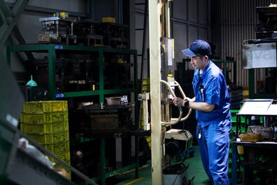 Japanese man wearing baseball cap and blue overall standing in factory, working at a machine.