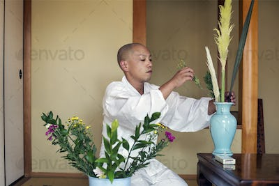 Buddhist monk with shaved head wearing white robe kneeling on floor, arranging flowers in blue vase.