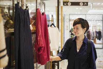 Woman with black hair wearing blue shirt standing indoors, looking at clothing in a shop.