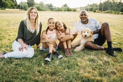 Portrait of mixed-race family in field with labradoodle puppy