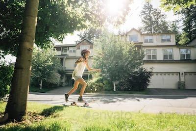 Tween Girl Skating on Skateboard on Sidewalk in Residential Neighborhood