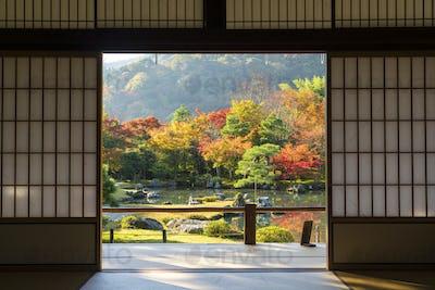 View through traditional Japanese sliding door into an autumn park landscape.