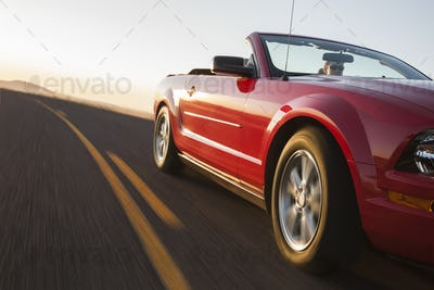 A low angle view of a convertible sports car moving on a highway late in the day.
