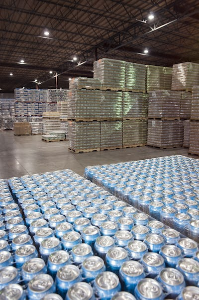 Cans of flavored water stored in the warehouse of a large bottling plant.