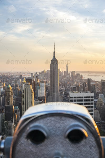 Cityscape of Manhattan at dusk, with coin operated binoculars in the foreground.