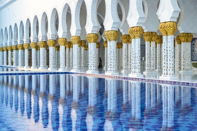 White colonnade of Sheikh Zayed Mosque and blue fountain, Abu Dhabi, United Arab Emirates.