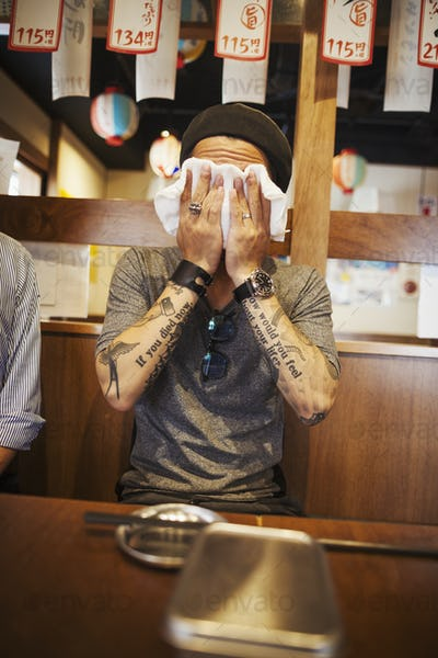 Man with tattooed arms sitting at a table in a restaurant, wiping his face with wet towel.