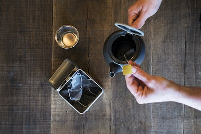 High angle close up of person adding tea bag to small black tea pot.