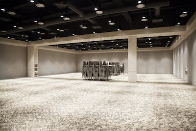 Stacked chairs in an empty convention center meeting room.