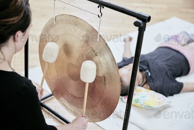 Woman striking a large gong wit soft drumsticks during a sound therapy session