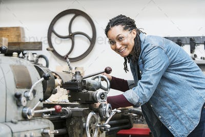 Smiling woman wearing safety glasses standing in a metal workshop at a machine, looking at camera.