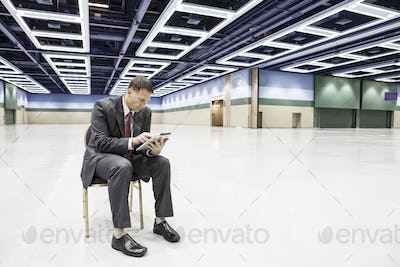 A caucasian businessman texting while sitting in a chair in the middle of a convention center arena.
