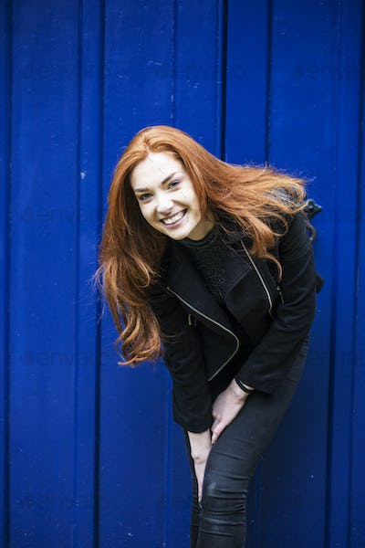 Portrait of smiling young woman with long red hair in front of bright blue door.