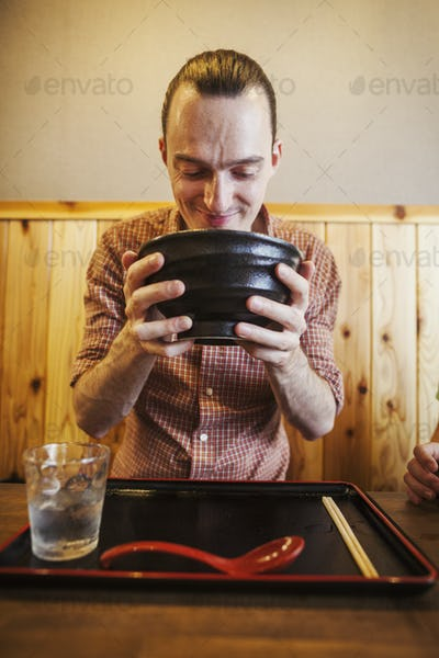 A western man in a noodle restaurant, with a noodle bowl lifting it with two hands to drink from it.