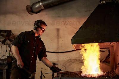 An artisan metal worker heating metal in a forge in his workshop.