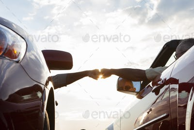 Fist bump between a passenger in one car and driver in another while cars are parked at a rest stop.