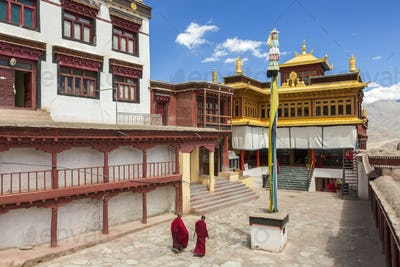 Exterior view of Buddhist monastery with two monks walking across courtyard.