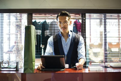 Japanese salesman standing at counter in clothing store, looking at digital tablet.