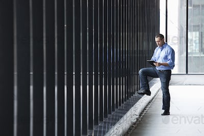 A Caucasian male architect standing by a wall of windows, using a digital tablet.