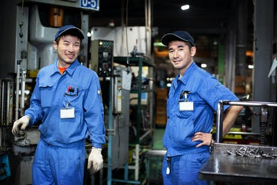 Two Japanese men wearing baseball caps and blue overalls standing in factory, smiling at camera.