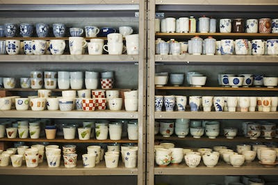 Large selection of ceramic cups and mugs on shelves in a Japanese porcelain workshop.
