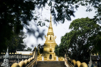 Exterior view of small local temple with golden stupa.
