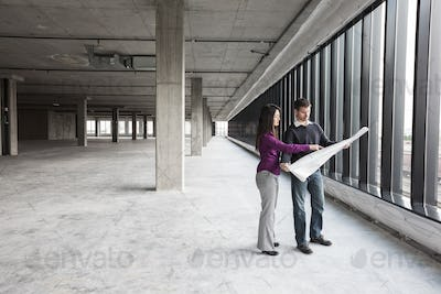 Two architects working on business plans in a new raw business space.