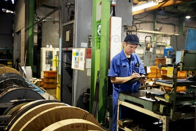 Japanese man wearing baseball cap and blue overall standing in factory, writing on clipboard.