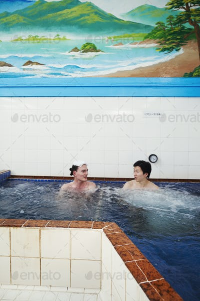 A young Caucasian man and Japanese man seated in a deep pool of moving water in a public bath house.