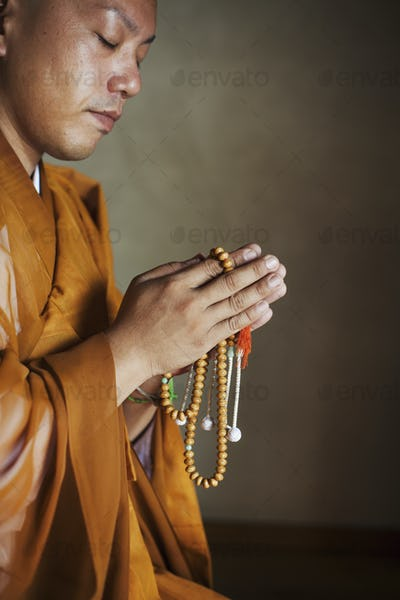 Side view of Buddhist monk wearing golden robe kneeling indoors in a temple, holding mala, praying.