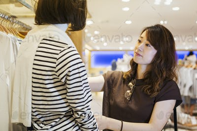 Woman with brown hair wearing brown shirt standing indoors, looking at clothing in a shop.