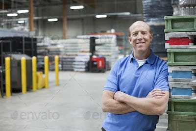 A portrait of a Caucasian male warehouse worker in a large warehouse facility.