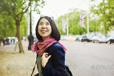 Smiling woman standing on the side of a tree-lined urban road.