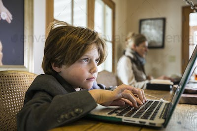 A six year old boy typing on a laptop at home