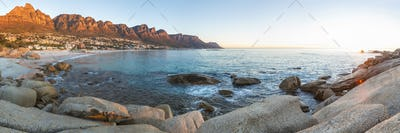 View along coastline with boulders and sandy beach, mountain range with twelve peaks lining bay.