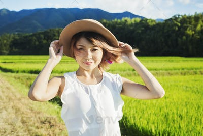 A young woman holding a straw hat on her head, hair blowing in the wind