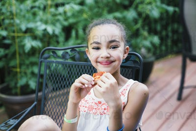Smiling girl eating pizza in backyard on porch