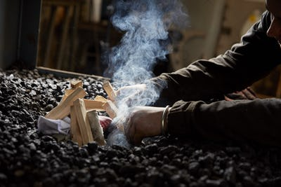 A metal worker lighting a furnace fire using wooden sticks and paper on top of a heap of coal.