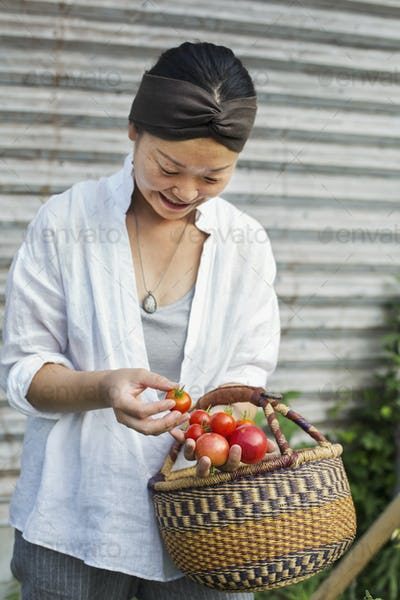 Smiling woman standing outdoors, holding basket and freshly picked tomatoes.