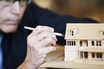 Caucasian male architect working on a scale model of a new home.