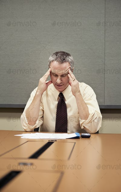 A Caucasian businessman sitting at a desk showing the stress of work.