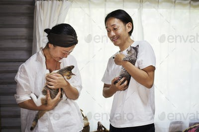 man and woman standing indoors, each holding calico cat with white, black and brown fur.