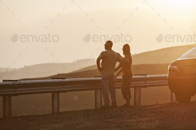 Senior couple watching a sunset from a rest stop on a road trip in eastern Washington State, USA.