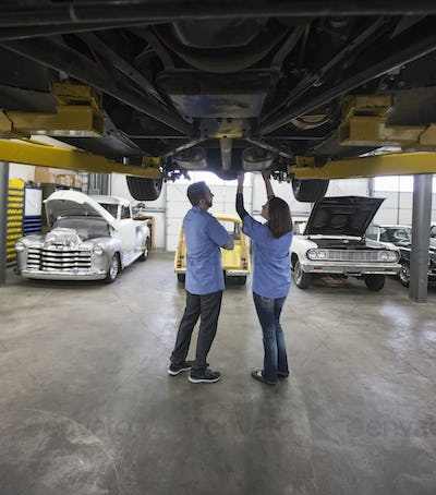 Male and female mechanics working on the underside of a car on a lift in a repair shop.