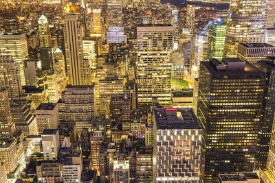 High angle view of central Manhattan, New York, USA, at dusk, with illuminated skyscrapers.