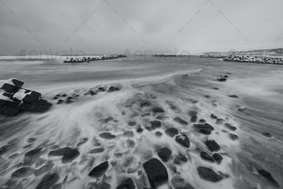 Snow-covered wave breakers on a rocky beach in winter.
