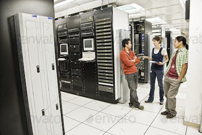 Three multi-ethnic technicians working in a large computer server room.