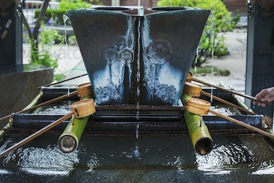 Close up of bamboo water hand washing basins at a Japanese Shinto Shrine.
