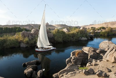 High angle view of sailboat on a river, rocks and sand hills in the distance.